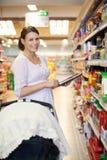 Mujer con la lista de compras en el ordenador de la tablilla Fotografía de archivo libre de regalías