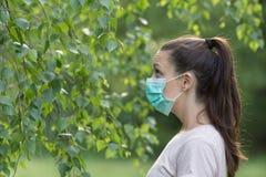 Mujer con la máscara al lado del árbol Fotos de archivo