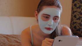 Mujer con la máscara cosmética en su cara metrajes