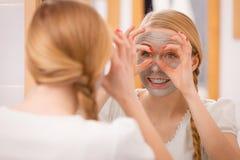 Mujer con la máscara del fango de la arcilla que se divierte Imagen de archivo