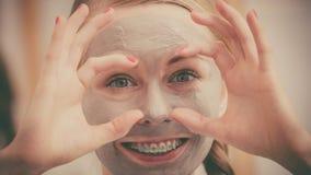 Mujer con la máscara del fango de la arcilla que se divierte Imágenes de archivo libres de regalías