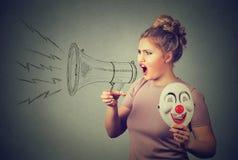 Mujer con la máscara del payaso que grita en megáfono imagen de archivo libre de regalías