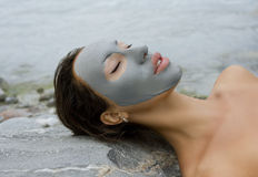 Mujer con la máscara facial de la arcilla azul en balneario de la belleza Imagenes de archivo