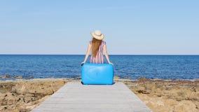 Mujer con la maleta en la playa metrajes