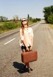 Mujer con la maleta, haciendo autostop a lo largo de un camino del campo Imagen de archivo