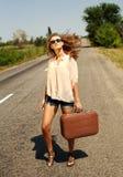 Mujer con la maleta, haciendo autostop a lo largo de un camino del campo Fotos de archivo libres de regalías