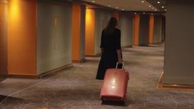 Mujer con la maleta que camina al cuarto en pasillo del hotel metrajes