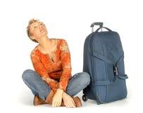 Mujer con la maleta que mira para arriba Foto de archivo libre de regalías