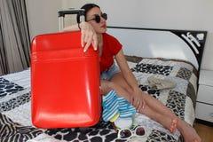 Mujer con la maleta que se sienta en cama en hotel La muchacha hermosa con una maleta del rojo ama viajar Imagen de archivo