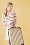 Mujer con la maleta y pasaporte que mira lejos contra vagos coloreados Fotografía de archivo