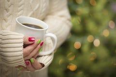 Mujer con la manicura roja y verde que sostiene la taza de café Fotos de archivo