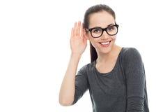 Mujer con la mano al oído que escucha Imagenes de archivo