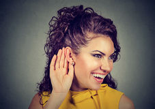 Mujer con la mano cerca del oído que escucha cuidadosamente y que sonríe imágenes de archivo libres de regalías