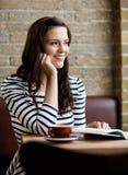 Mujer con la mano en Chin Looking Away In Cafeteria Fotografía de archivo libre de regalías