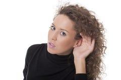 Mujer con la mano en su oído Imagen de archivo libre de regalías