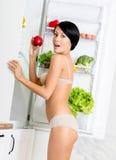 Mujer con la manzana roja cerca del refrigerador abierto Fotografía de archivo libre de regalías