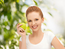 Mujer con la manzana verde en el campo Foto de archivo