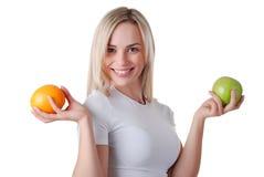 Mujer con la manzana y la naranja verdes fotografía de archivo libre de regalías