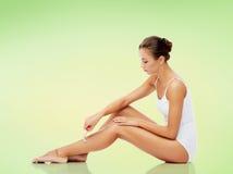 Mujer con la maquinilla de afeitar de seguridad que afeita las piernas Fotos de archivo libres de regalías