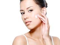 Mujer con la mirada sensual que aplica la crema en su cara Fotos de archivo