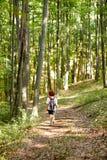 Mujer con la mochila en el bosque imagenes de archivo