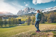 Mujer con la mochila en valle de la monta?a en la puesta del sol en primavera fotografía de archivo libre de regalías