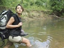 Mujer con la mochila que camina en Forest Water Fotografía de archivo