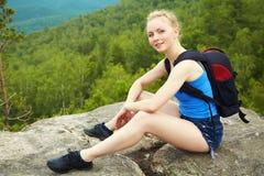 Mujer con la mochila que camina en las montañas imagen de archivo