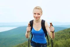 Mujer con la mochila que camina en las montañas fotografía de archivo libre de regalías