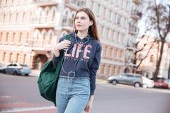 Mujer con la mochila que escucha la música y que camina en ciudad Fotografía de archivo