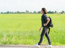 Mujer con la mochila que hace autostop a lo largo de un camino Imagenes de archivo