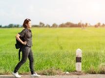 Mujer con la mochila que hace autostop a lo largo de un camino Imagen de archivo