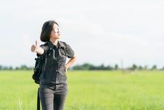Mujer con la mochila que hace autostop a lo largo de un camino Fotos de archivo libres de regalías