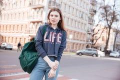 Mujer con la mochila que se coloca cerca del camino en la ciudad Imágenes de archivo libres de regalías
