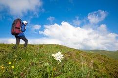 Mujer con la mochila turística en la montaña Fotos de archivo