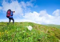 Mujer con la mochila turística en la montaña Imagen de archivo