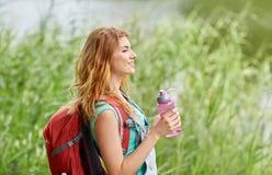 Mujer con la mochila y la botella de caminar del agua Foto de archivo