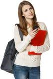 Mujer con la mochila y los libros con el teléfono celular Fotos de archivo