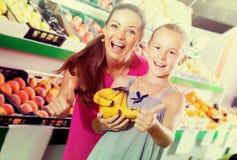 Mujer con la muchacha que sostiene los pulgares para arriba en tienda de la fruta Foto de archivo libre de regalías