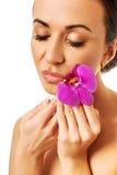 Mujer con la orquídea púrpura y los ojos cerrados Foto de archivo libre de regalías