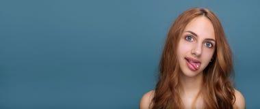 Mujer con la píldora en su lengua aislada en fondo gris Fotografía de archivo libre de regalías