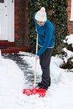 Mujer con la pala de la nieve Foto de archivo