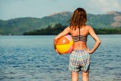 Mujer con la pelota de playa en la playa Fotos de archivo libres de regalías
