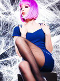 Mujer con la peluca púrpura y el maquillaje intenso atrapados en un Web de araña Fotografía de archivo
