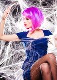 Mujer con la peluca púrpura y el maquillaje intenso atrapados en un Web de araña Fotografía de archivo libre de regalías