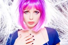Mujer con la peluca púrpura y el maquillaje intenso atrapados en un Web de araña Imágenes de archivo libres de regalías