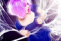 Mujer con la peluca púrpura y el maquillaje intenso atrapados en un Web de araña que grita Imagen de archivo libre de regalías