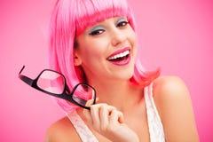 Mujer con la peluca y los vidrios rosados Foto de archivo libre de regalías