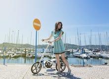 Mujer con la pequeña bicicleta moderna Imagen de archivo