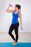 Mujer con la pesa de gimnasia que se coloca en la estera del ejercicio fotografía de archivo